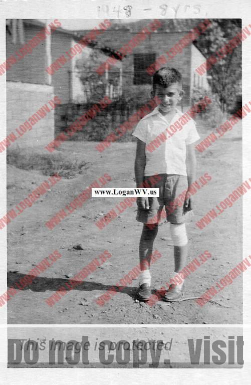 1948 Bobby McCormack - 8 years old in back alley, The ESSO station in the background