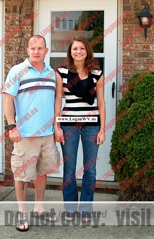 Robb McCormack and Olivia McCormack in front of their first home in Hurricane, WV.