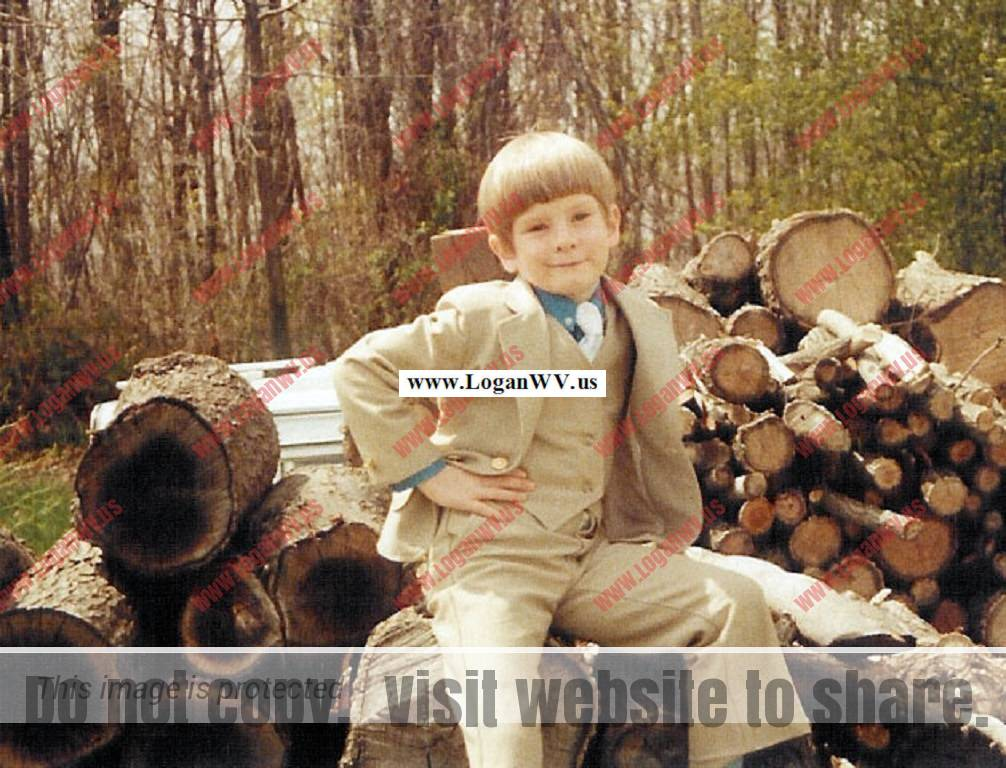 Robb McCormack in his Sunday best sitting on a wood pile at his home in Mt. Airy, MD.