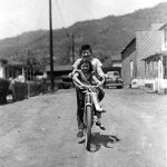 Bobby McComack riding his bike in the back alley.  George Hannah & Hubert Raikes homes in the background