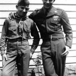 Bobby McCormack in scout uniform & Ron McCormick in Army uniform in the McCormack back yard.