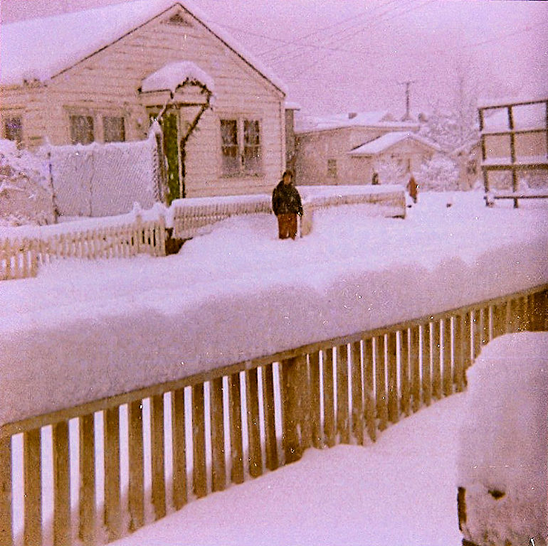 Ann Szakal in front of Elsie Szaka'sl home. Dexter Webb home and Carver home in background. Dec 30 1970