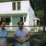 Jessie Blankenship with her mother Goldie Grimmett. Taken in the yard of Hobert Raikes. George Hannah home in background.